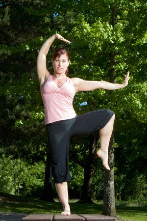 Physically fit woman standing on picnic table in the park. Posed in karate stance, balanced on right foot. Vertically framed shot.