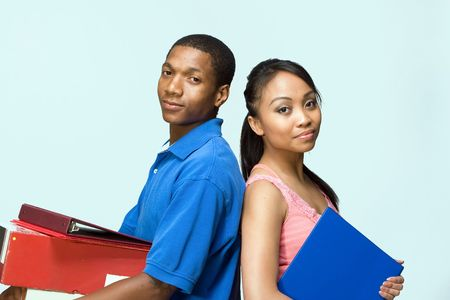 Two students standing back to back carrying books. Horizontally framed photograph photo