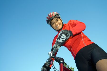 Close-up of woman standing next to bicycle, looking down and smling. Wearing sports gear and helmet. Horizontally framed shot.