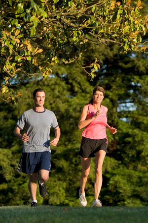 A young couple go jogging around a park with each other, smiling. - vertically framed Stockfoto