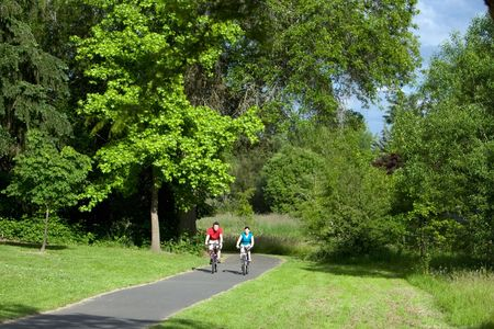 A far shot of a couple riding bicycles on a park trail together, smiling. - horizontally framed Stock Photo
