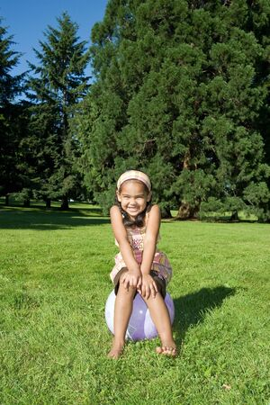 A young girl, sitting on a ball, in a field of grass in a park, smiles big. - vertically framed Stock Photo - 3284668