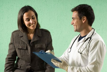 A young doctor showing a patients results on his clipboard, smiling. - horizontally framed Stock Photo
