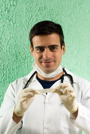 A young doctor is standing in his office.  He is holding up a plaster.  He is smiling and looking at the camera.  Vertically framed photo.