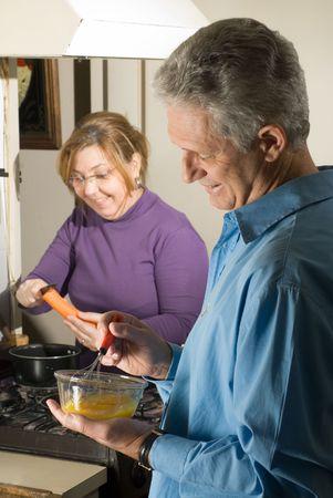 Una pareja haciendo el desayuno, el hombre whisking huevos, la mujer de corte las zanahorias en la cocina, sonriendo. - Enmarcada verticalmente Foto de archivo - 3284583