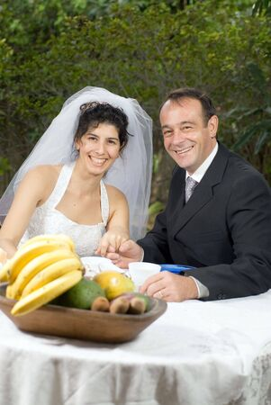 vertically: A newly married couple, at a table with fruits on it, smile for the camera together. - vertically framed Stock Photo