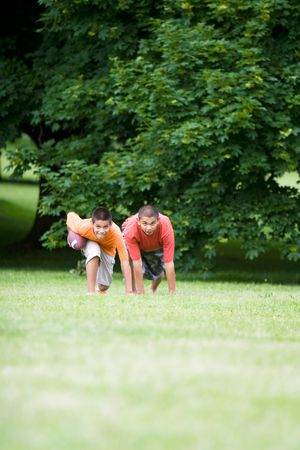 Two young boys, one holding a football prepare to race across a field of grass. - vertical photo