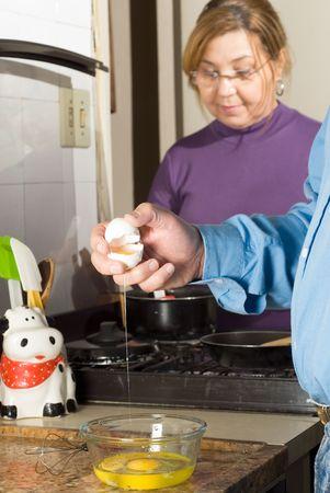 Una pareja en la cocina, haciendo el desayuno, el hombre de craqueo huevos. - Enmarcada verticalmente Foto de archivo - 3284555
