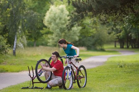 summer tire: A man, takes his bicycle tire off, while a woman on her bike, stands behind him watching. - horizontally framed Stock Photo