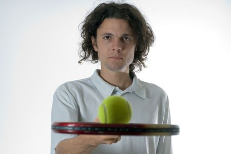 bore: Man wearing a serious expression on his face holds a tennis racket and balances a tennis ball on top of it. Horizontally framed photograph Stock Photo
