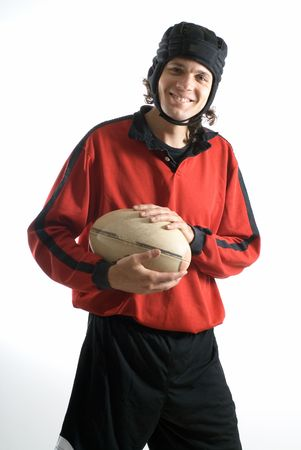 vertically: Rugby player smiles as he holds a football - Vertically framed photograph Stock Photo