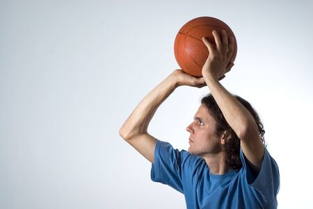 concentrating: Man concentrating on shooting basketball. Horizontally framed photograph.