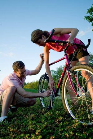 Man and woman fixing a bike. Vertically framed shot. photo