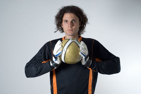 Soccer goalie holds a soccer ball with his goalie gloves and has a serious expression on his face. Horizontally framed photograph Banco de Imagens