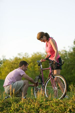 crouches: Woman holding on to her bike while the man crouches down to inspect it. Vertically framed photograph Stock Photo