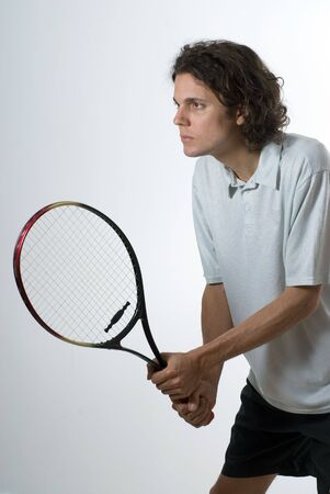 vertically: A tennis player holding a racket and staring intensely into the unseen distance. Vertically framed shot.