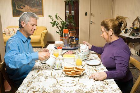 Een paar, zitten aan een tafel, thee gieten, met hun ontbijt voor hen. - Horizontaal omlijst