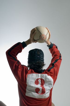 vertically: A man, wearing a number 3 on his rugby jersey, prepares to throw the rugby ball. Vertically framed shot. Stock Photo