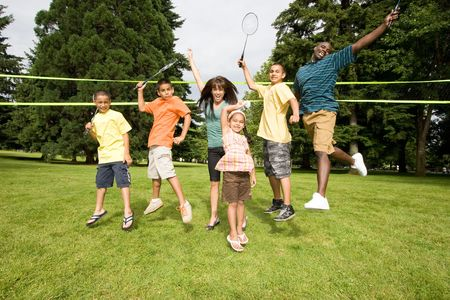 A happy family jump at the same time together, with rackets in air. - horizontally framed photo