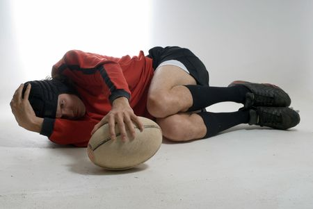 fetal: A man, wearing a full rugby outfit, lies down on the ground in the fetal position, putting his hands on the ball. Horizontally framed shot. Stock Photo