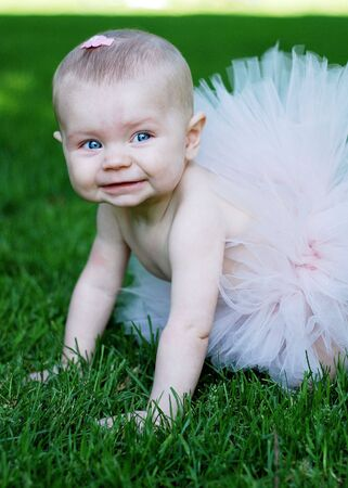A baby, crawling in the grass, wearing a pink tutu, smiling. Vertically framed shot. Stock Photo - 3329215
