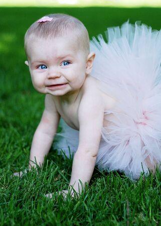 bebe gateando: Un beb�, el rastreo en el c�sped, el uso de un tut� rosa, sonriendo. Enmarcada verticalmente disparo.