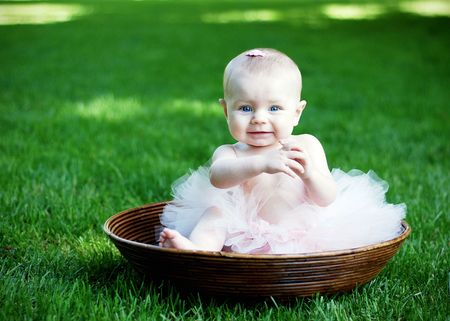 A young baby, wearing a pink tutu and bow in her hair, sits in a wooden bowl, staring at the camera. Horizontally framed shot. Stock Photo