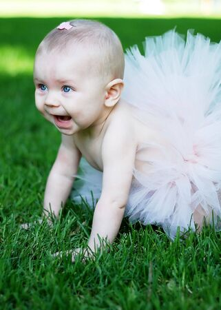 A young baby, crawling through a grassy field, laughs and smiles, while wearing a pink tutu and bow. Vertically framed shot. photo
