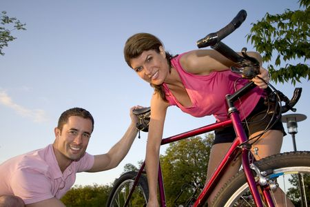 Smiling man and woman fixing a bike. Horizontally framed shot. photo