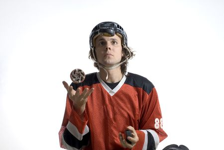 tosses: Rugby player wearing a helmet and uniform tosses a hockey puck in his hand. Horizontally framed photograph Stock Photo