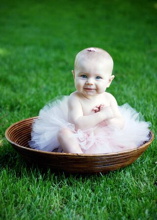 A young baby, sitting in a wooden bowl, laughs and smiles, while wearing a pink tutu and bow. Vertically framed shot. photo