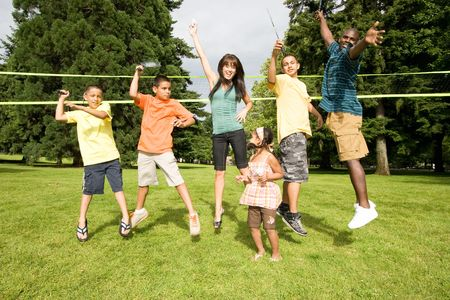 simultaneously: A happy family jump simultaneously, some pretending to play badminton. - horizontally framed Stock Photo