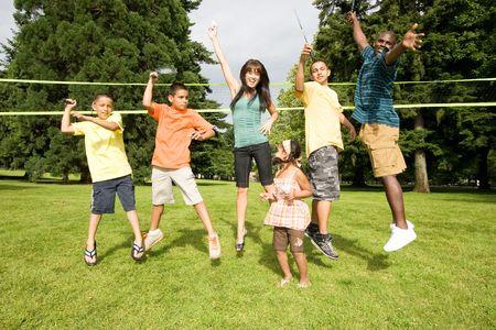 Een gelukkig gezin springen tegelijk, sommige pretenderen te spelen badminton. - Horizontaal omlijst