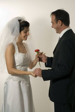 midlife: A pair of newly weds, hold hands, the man giving the woman a single, red rose. - vertically framed