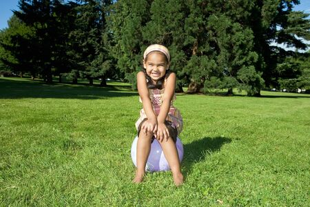 A young girl smiles big while in a park, sitting on a ball. - horizontally framed Stock Photo - 3330236