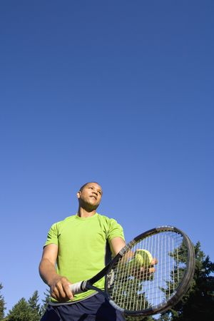A man is standing outside on a tennis court.  He is holding a tennis racket, about to hit the tennis ball, and looking away from the camera.  Vertically framed shot. 免版税图像