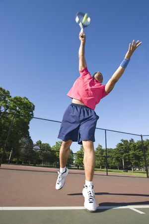 A man is outside on a tennis court playing tennis.  He is about to serve the ball and is looking away from the camera.  Vertically framed shot. Stock Photo - 3334457