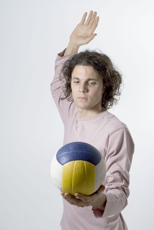 Man holds a volleyball in one hand and raises his other hand to serve it. Vertically framed photograph Banco de Imagens