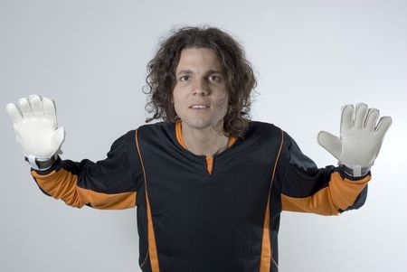 An athlete posing in a goalie stance.  His hands are gloved and he has his arms stretched out defensively. Horizontally framed shot.