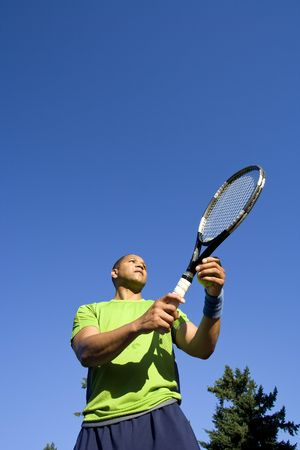 A man is standing outside on a tennis court.  He is holding a tennis racket and looking away from the camera.  Vertically framed shot. Stock Photo - 3338734