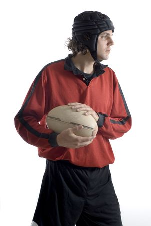A young man, stands in a rugby outfit, holding on to the ball with both hands, looking away. Vertically framed shot. Stock Photo