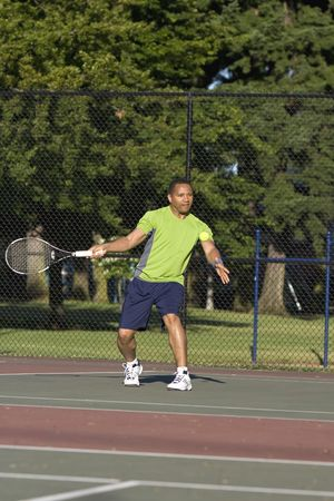 A man is outside on a tennis court playing tennis.  He is about to hit the ball and is looking away from the camera.  Vertically framed shot. Stock Photo - 3338993