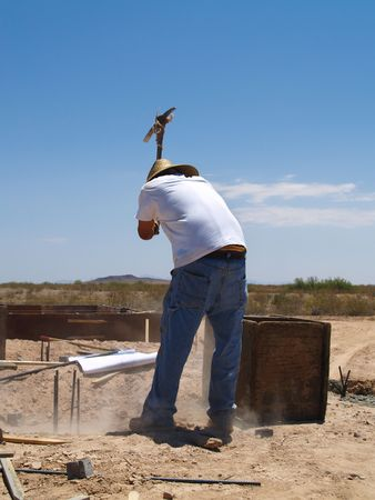 A construction worker is working on an excavation site.  He is about to swing a pickaxe into the ground.  Vertically framed shot. Stock Photo - 3338903