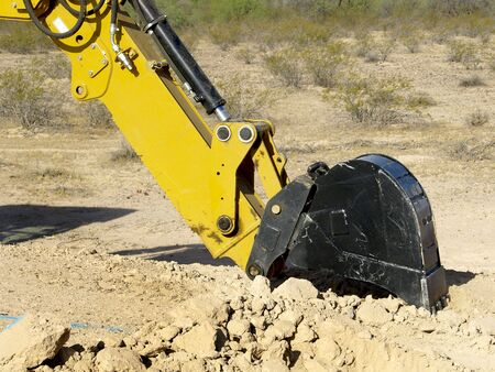 A giant steam shovel is about to dig into the dirt.  Horizontally framed shot.