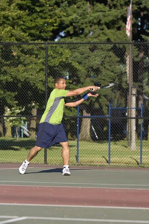 A man is outside on a tennis court playing tennis.  He is looking at the tennis ball after he just hit it with his racket.  Vertically framed shot.