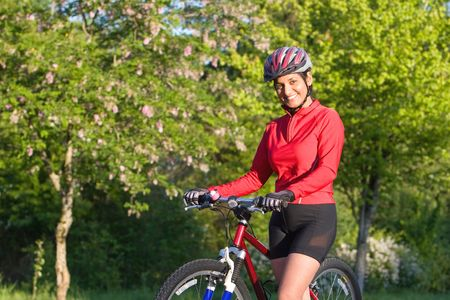 Close-up of woman standing next to bicycle in park and smiling. Wearing sports gear and helmet. Horizontally framed shot. photo