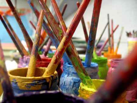 horizontally: Paintbrushes are covered with different colored paints.  They are sitting in jars.  Horizontally framed shot.