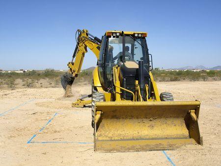 A giant steam shovel is digging up dirt.  Horizontally framed shot.