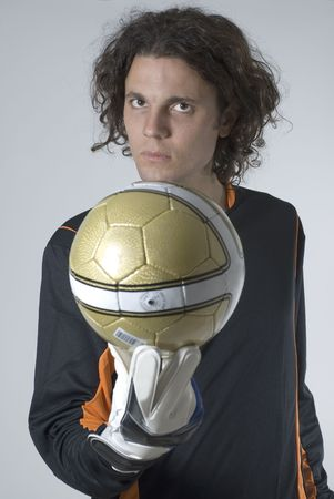 Man with a serious expression holds a soccer ball out in front of him. Vertically framed photograph.