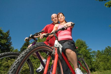 A couple sitting close to each other while on a pair of bikes, on a sunny day, at a park. - horizontally framed photo